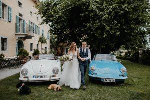 Ženin in nevesta ob poročnih avtomobilih.