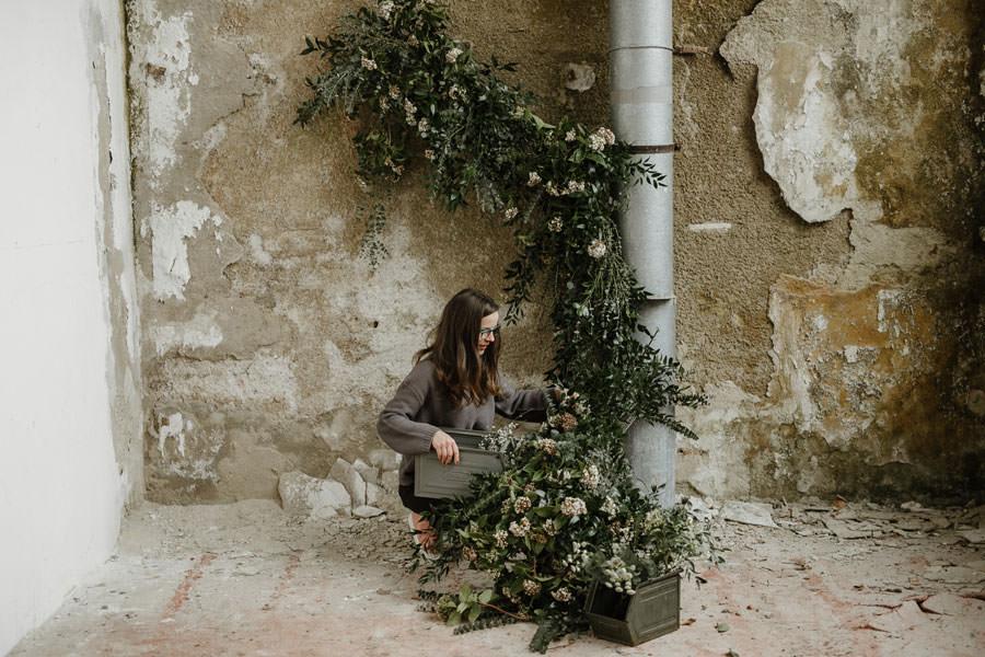 Floristka obeša na žleb zeleno cvetje