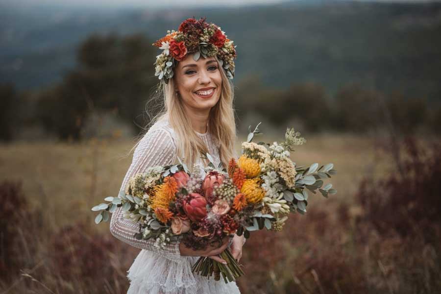 Nevesta s trendovskim poročnim šopkom in cvetjem v laseh