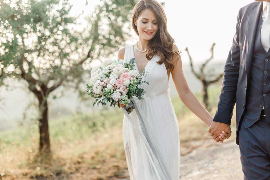 Couple walking down the aisle. Bride with the trend wedding bouquet
