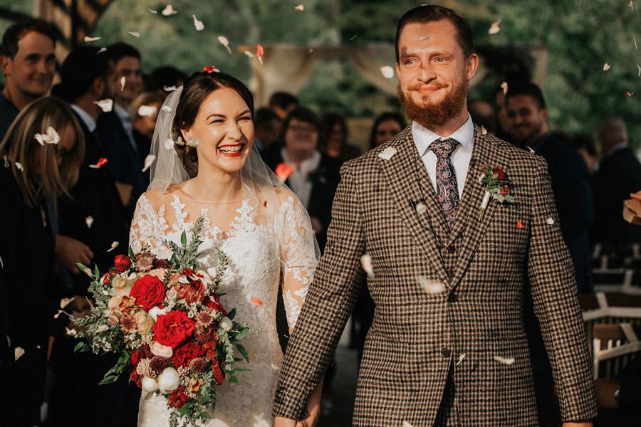 Poročni par z rdečim poročnim šopkom