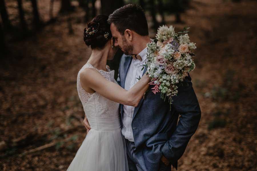 poročni par v objemu Nevesta drži trendovski poročni šopek