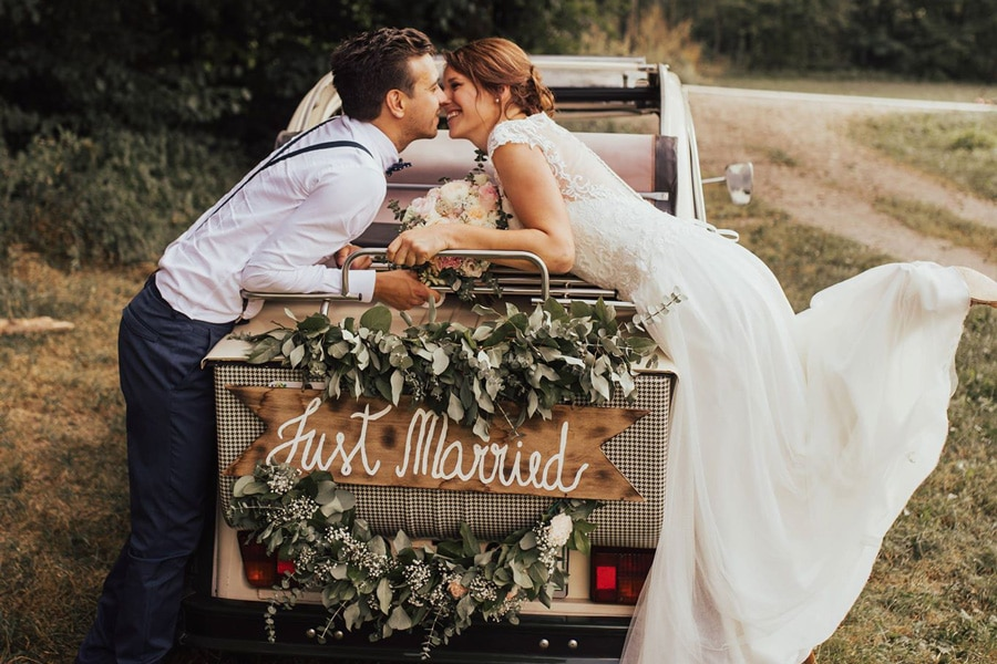 poročni par naslonjen na zadnji del avtomobila z minimalistično cvetlično dekoracijo