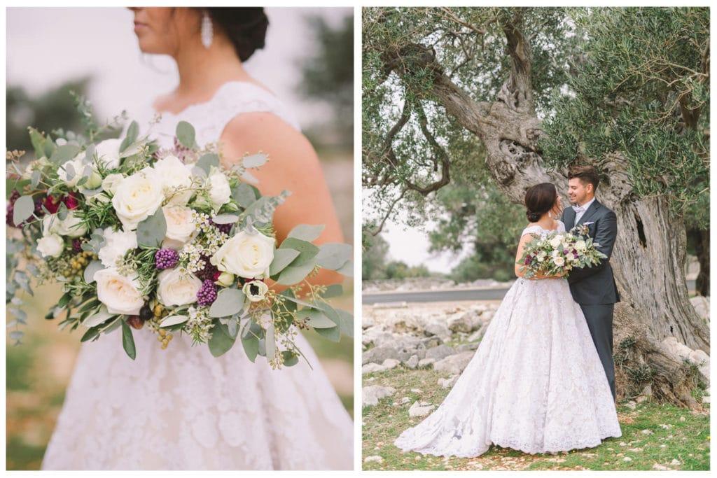 Nevesta v objemu ženina z elegantnim poročnim šopkom pod staro oljko