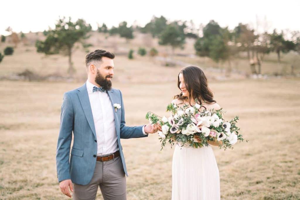 Ženin in nevesta s pomladnim šopkom se držita za roko