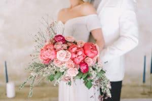 ženin objema nevesto s poročnim šopkom iz koralnih potonik
