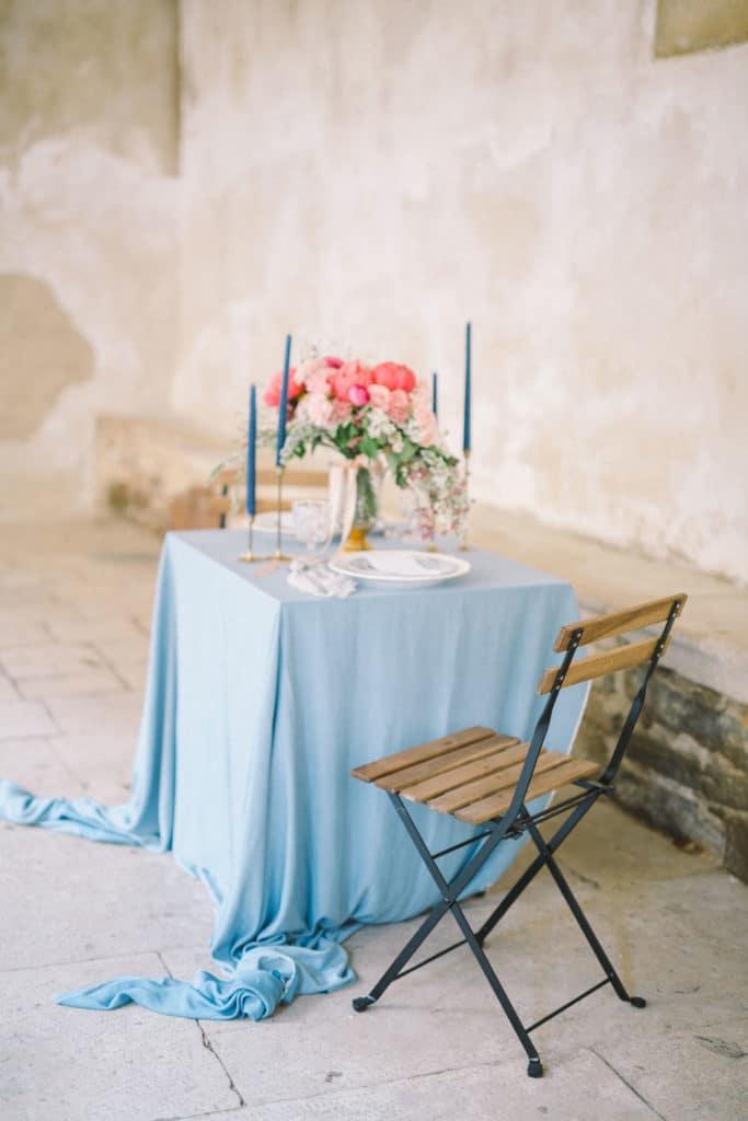Poročna miza za dva z modrim prtom in cvetlično dekoracijo