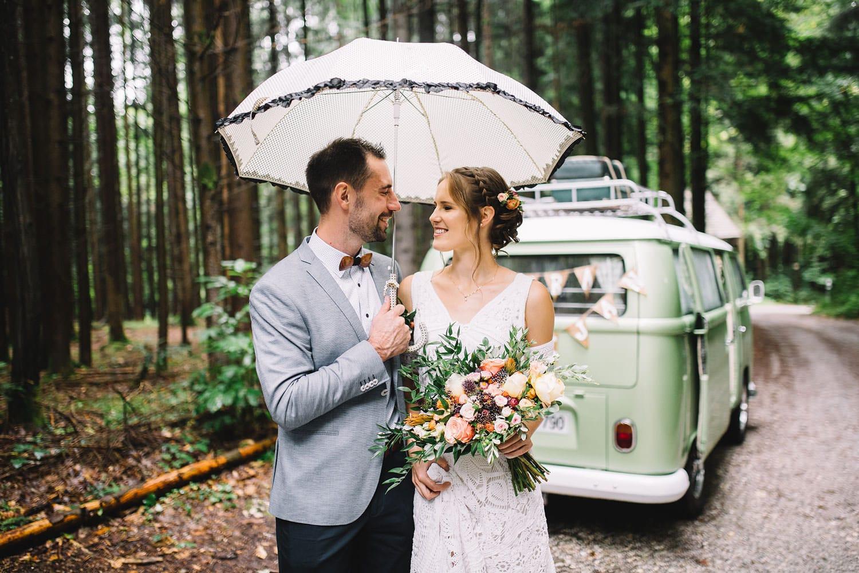 Ženin in nevesta stojita v gozdu ob vw t2 kombiju s poročnim šopkom v boho stilu