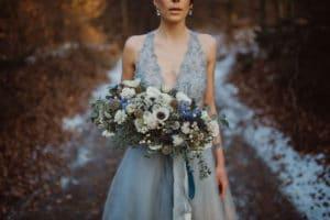 Nevesta v modri poročni obleki in z zimskim poročnim šopkom