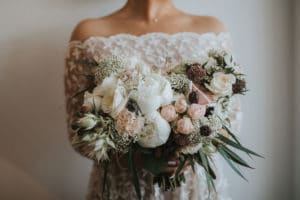 Nevesta drži eleganten poročni šopek s potonikami in angleškimi vrtnicami