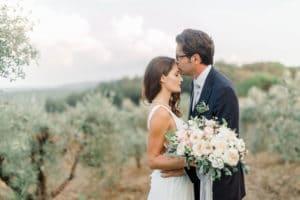 Nevesta in ženin v objemu z modernim poročnim šopkom na posestvu Toskanske domačije