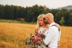 Nevesta in ženin stojita v objemu na travniku z divjim poročnim šopkom