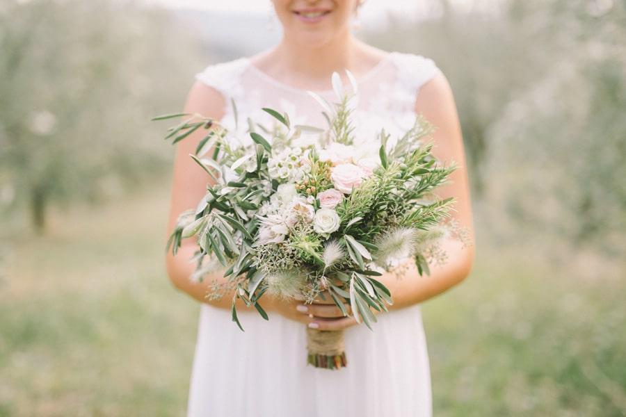 Poročni šopek iz oljke in rožmarina drži v roki nevesta, ki stoji na travniku.