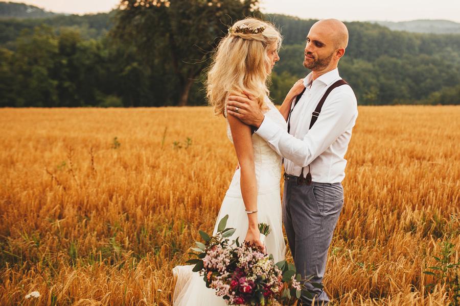 Barvit Poročni šopek v rokah neveste, ki je v objemu ženina in stojita na travniku