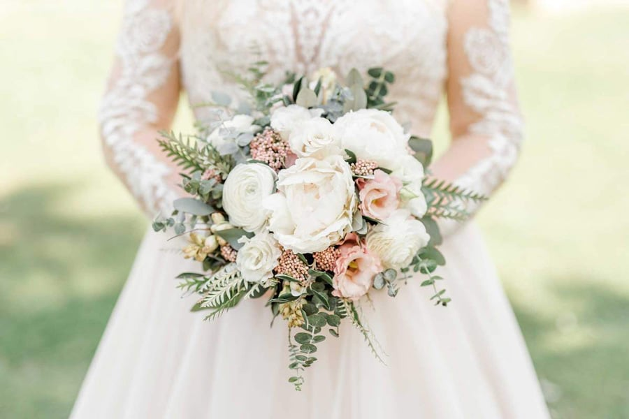 Pomladni poročni šopek v rokah neveste